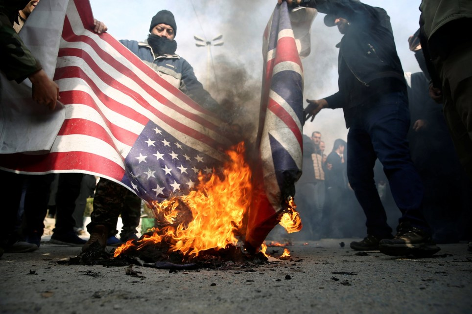 Demonstrators burn the U.S. and British flags during a protest against the assassination of the Iranian Major-General Qassem Soleimani, head of the elite Quds Force, and Iraqi militia commander Abu Mahdi al-Muhandis who were killed in an air strike in Baghdad airport, in Tehran, Iran January 3, 2020. WANA (West Asia News Agency)/Nazanin Tabatabaee via REUTERS ATTENTION EDITORS - THIS IMAGE HAS BEEN SUPPLIED BY A THIRD PARTY.