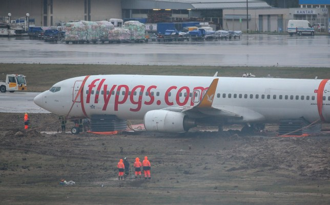 ISTANBUL, TURKEY - JANUARY 7: Workers try to remove a plane after it skidded off runway while landing at Sabiha Gokcen International Airport in Istanbul, Turkey on January 7, 2020. The incident happened at 9.43 a.m. local time (0643GMT) when a Pegasus Airline plane coming from the UAEs Sharjah International Airport skidded due to bad weather, according to the Istanbul Governors Office. (Photo by Muhammed Enes Yildirim/Anadolu Agency via Getty Images)