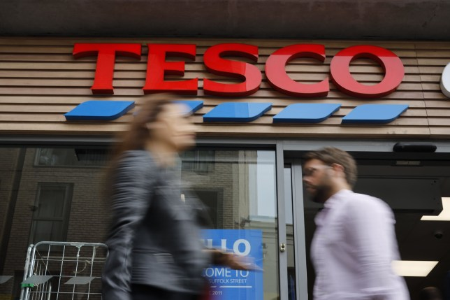 (FILES) In this file photo taken on September 30, 2019 people walk past a Tesco Express in central London on September 30, 2019. - Tesco, Britain's biggest food retailer had its best ever day of food sales despite a challenging year as it unveiled its Christmas sales figures on January 9, 2019. (Photo by Tolga AKMEN / AFP) (Photo by TOLGA AKMEN/AFP via Getty Images)