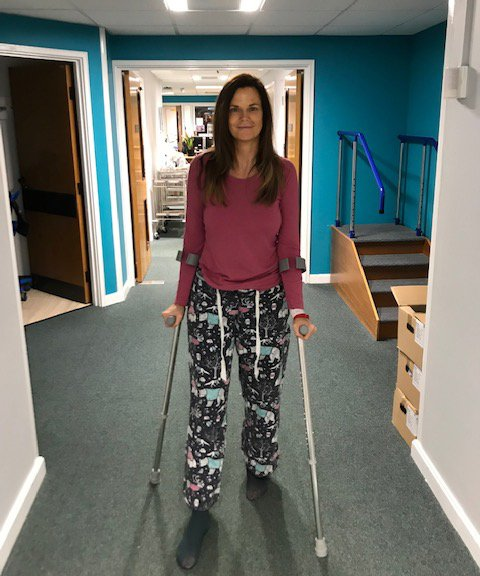 Carolyne on crutches, in hospital recovering from her hip operation