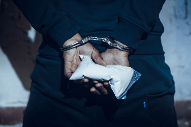 Male hands in handcuffs holding bag of cocaine