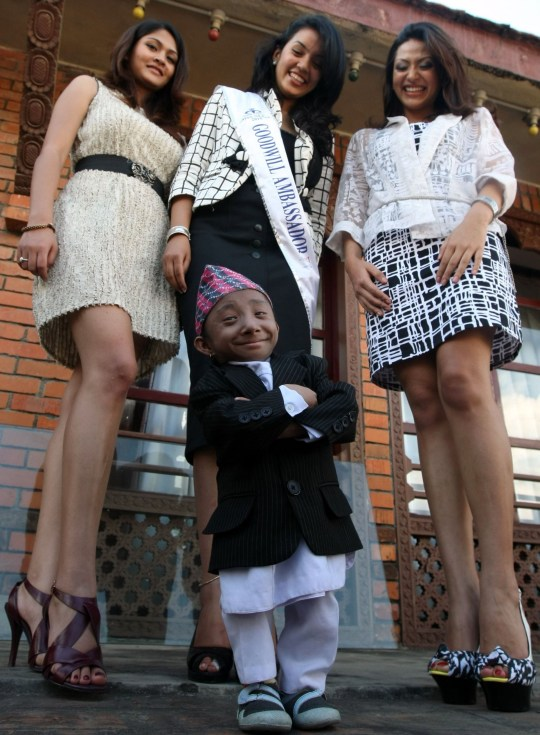 (FILES) In this file photo taken on September 24, 2010 Nepalese teenager Khagendra Thapa Magar poses for a picture with Miss Nepal Sadichha Shrestha (C) and first runner-up Sahana Bajracharya (R) and second runner-up Samyukta Timilsina (L) in Kathmandu. - The world's shortest man who could walk, as verified by Guinness World Records, died on January 17, 2020 at a hospital in Nepal, his family said. Khagendra Thapa Magar, who measured 67.08 centimetres (2 feet 2.41 inches), died of pneumonia at a hospital in Pokhara, 200 kilometres from Kathmandu, where he lived with his parents. (Photo by Prakash MATHEMA / AFP) (Photo by PRAKASH MATHEMA/AFP via Getty Images)