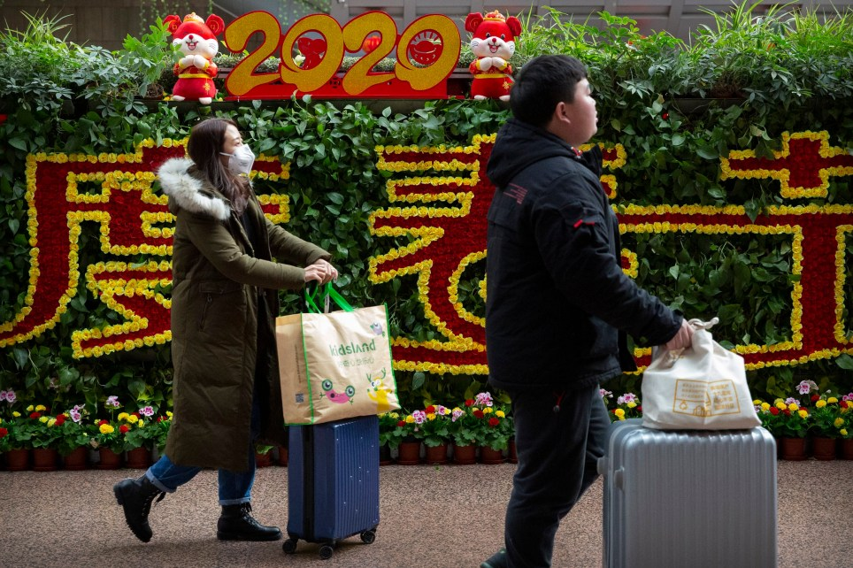A traveler wearing a face mask walks past a display for the upcoming Lunar New Year, the Year of the Rat, at the Beijing West Railway Station in Beijing, Tuesday, Jan. 21, 2020. A fourth person has died in an outbreak of a new coronavirus in China, authorities said Tuesday, as more places stepped up medical screening of travelers from the country as it enters its busiest travel period. (AP Photo/Mark Schiefelbein)