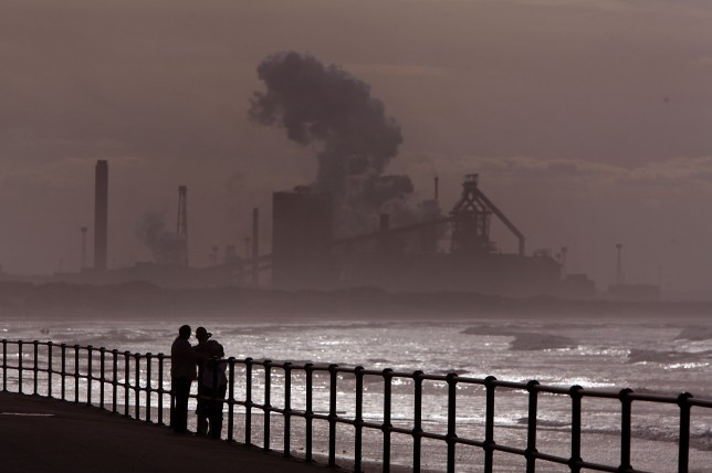 MIDDLESBOROUGH, UNITED KINGDOM - JULY 21: People look out over Redcar beach in the shadow of the Corus Steelworks in Teeside, on July 21, 2008, in Middlesborough, England. The giant iron and steel works on the south bank of the River Tees produces 3.4 million tonnes of slab steel a year. (Photo by Christopher Furlong/Getty Images)