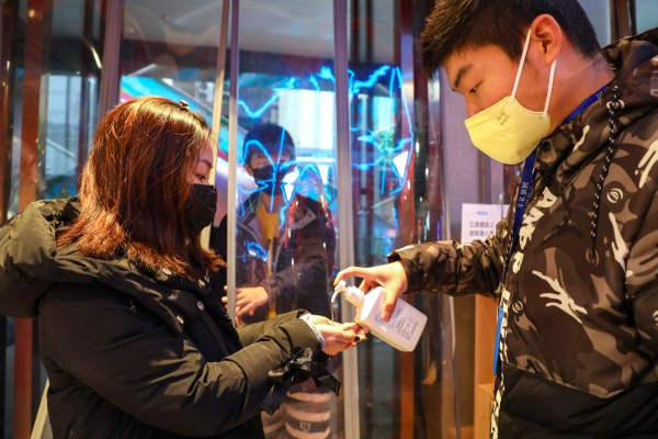 A worker dispenses hand sanitizer to a shopper at the entrance of a supermarket in Wuhan in central China's Hubei province, Saturday, Jan. 25, 2020. The virus-hit Chinese city of Wuhan, already on lockdown, banned most vehicle use downtown and Hong Kong said it would close schools for two weeks as authorities scrambled Saturday to stop the spread of an illness that is known to have infected more than 1,200 people and killed 41, according to officials. (Chinatopix via AP)