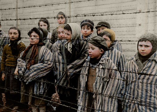 POLAND: Harrowed children at Auschwitz, in a still from the Soviet film of the liberation of Auschwitz, January 1945. HARROWING colourised images of the Holocaust which expose the full terrors faced by the death camp?s inmates have emerged SEVENTY-FIVE-YEARS after the liberation of Auschwitz, the largest Nazi death camp. Sobering photos, some revamped in colour for the first time, capture the horror of genocide in the eyes of a gaunt 18-year-old Russian woman; a concentration camp responsible for the deaths of tens of thousands of innocent people being ceremonially burnt to the ground by liberating British forces; and malnourished Jewish children peering out at their Soviet rescuers through a barbed wire fence at Auschwitz. Other upsetting colourisations include a smiling portrait of four-year-old, Istvan Reiner, taken just a few weeks before he was murdered at the infamous death camp, and another showing a palpably relieved young Jewish refuge recuperating in hospital after being rescued by appalled Allied Forces. Mediadrumimages/TomMarshall(PhotograFix)2020
