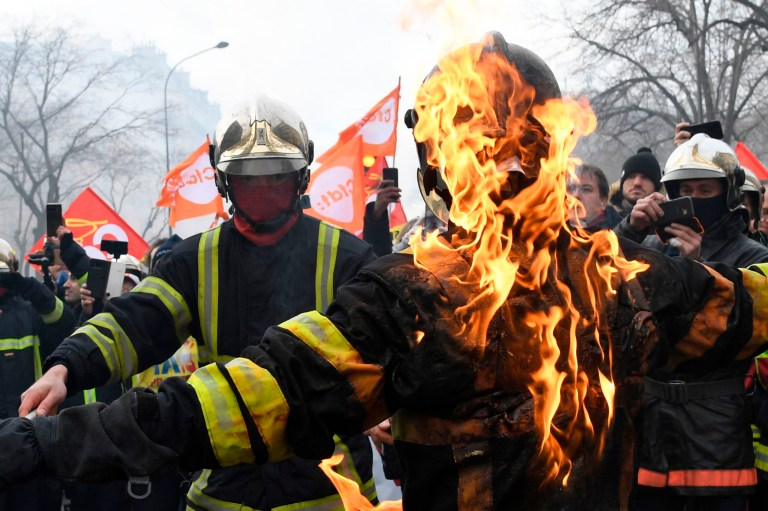 A firefighter sets alight another one as they take part in a demonstration to protest against French government's plan to overhaul the country's retirement system in Paris, on January 28, 2020. (Photo by Bertrand GUAY / AFP) (Photo by BERTRAND GUAY/AFP via Getty Images)