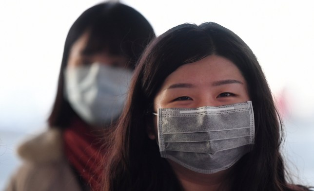 epa08175754 People wear face masks at Heathrow Airport in London, Britain, 29 January 2020. British Airways has announced it has suspended all flights to and from mainland China due to the threat of the coronavirus. Flights from the virus hit areas within China may begin bringing home Britons this coming Thursday. EPA/ANDY RAIN