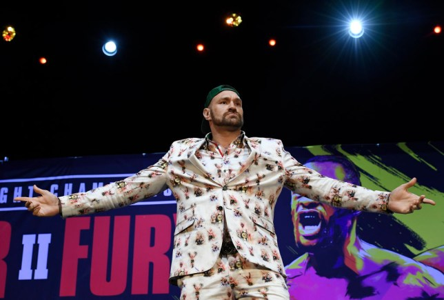 Tyson Fury spreads hims arms as he poses for pictures at a boxing press conference