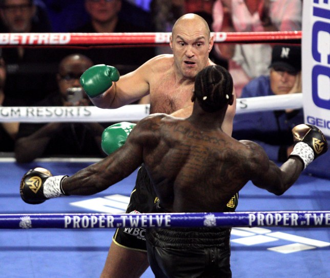 Tyson Fury punches Deontay Wilder during their heavyweight fight