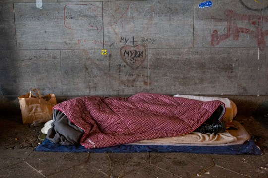 A homeless person sleeping in sleeping bags