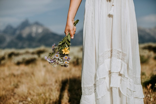 close up of bride with wildflower bouquet in front of Tetons, Wyoming