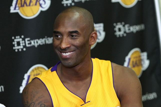 Basketball star Kobe Bryant smiles as he speaks to the media