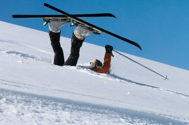 A skier who has fallen over lying in powder