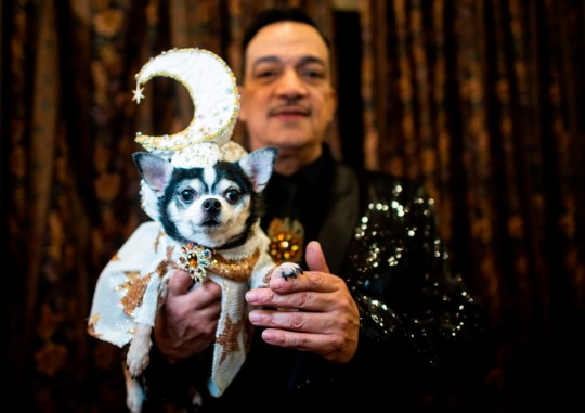 A dog owner holds his dog dressed up for a show at the 17th annual New York Pet Fashion Show