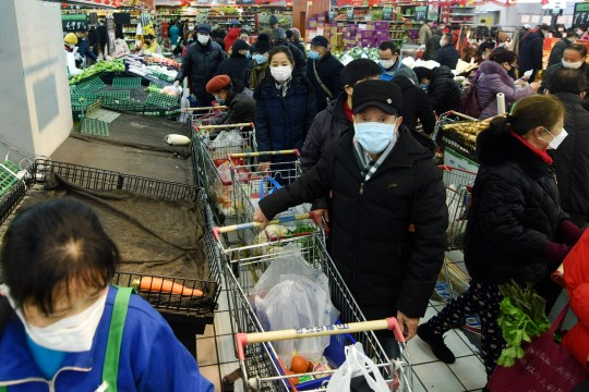People wearing masks buy foods at a supermarket in Hangzhou in east China's Zhejiang province, Saturday, Feb. 8, 2020.
