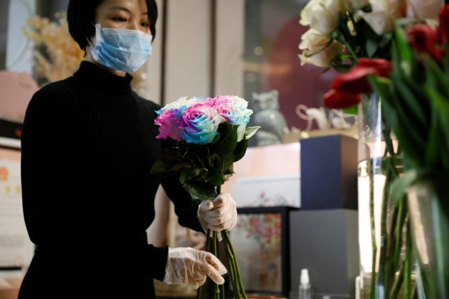 A florist who prefers to be called Cai Xiaoman wearing a face mask and gloves, ensembles a bouquet at a flowers shop in a shopping mall, as the country is hit by an outbreak of the new coronavirus, in Beijing, China February 13, 2020. REUTERS/Carlos Garcia Rawlins