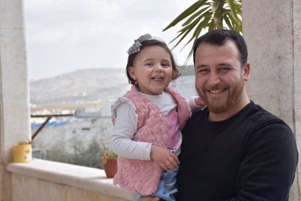 IDLIB, SYRIA - FEBRUARY 17: 4 year old Syrian girl Salva poses for a photo with her father Abdullah Muhammed during an exclusive interview after a video on social media showing her father has taught to her to laugh each time they hear a bombing or warplane noise, went viral, in Idlib, Syria on February 17, 2020. (Photo by Mehmet Burak Karacaoglu/Anadolu Agency via Getty Images)
