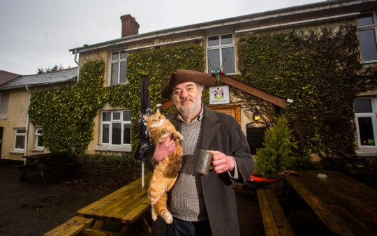"Landlord Steve Cotten at the Poltimore Arms in Exmoor. See SWNS story SWPLpub; Meet Britain's wackiest landlord who models himself on an outlaw, has forced Prince Harry to pull his own pints - and has a pub cat named HITLER. Wacky Steve Cotten, 59, saved the historic Poltimore Arms pub seven years ago - but after a career in precision engineering he admitted he had no idea how to run a boozer. He initially told no-one he had opened and enjoyed getting drunk alone by the fire - but soon his brash and unorthodox manner created a buzz and the crowds began to flock back. The pub - which is fully off-grid and lays claim to the greenest in the UK - has now become a favorite among royals and celebrities who frequent the area for shooting and hunting events. Among the clientele are film producers, billionaires, royalty, formula one stars and business heavyweights. But Steve said it doesn't matter who comes through the doors - he is equally abusive to everyone - and tells all customers to serve themselves. Inside the pub there several rooms adorned with bizarre decor - one with multiple pianos - but it is the unique welcome that stands Steve out from the rest. He models himself on Dick Turpin with full attire including jacket, hat and gun - as he has been raided six times by HMRC who believe the pub is more profitable than it is. Steve said that while he has never made any money from his venture he believes he has created something special in a remote corner of Exmoor, despite the nearest neighbour being a mile away. And all visitors are also greeted by the resident ginger moggy named Frederick Albert Hitler after Steve requested the ""nastiest"" cat they had at a rescue centre."