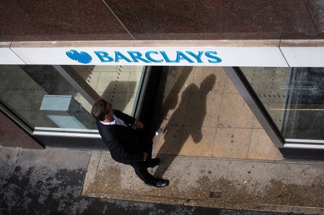 A visitor passes beneath a Barclays logo as he enters a Barclays Plc bank branch in London, U.K., on Wednesday, May 7, 2014. Barclays will cut 7,000 jobs at its investment bank, bringing the total number of jobs to be cut across the firm by 2016 to 19,000, including the 12,000 the lender announced in February it would cut this year, Barclays said in a statement. Photographer: Simon Dawson/Bloomberg via Getty Images