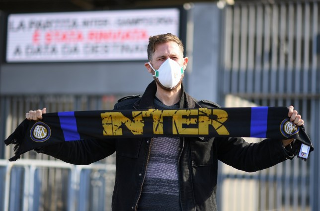 A man wearing a face mask stands outside the San Siro stadium after the Inter Milan v Sampdoria Serie A match was cancelled
