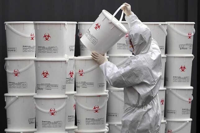 "A worker in protective gear stacks plastic buckets containing medical waste from coronavirus patients at a medical center in Daegu, South Korea, Monday, Feb. 24, 2020. South Korea reported another large jump in new virus cases Monday a day after the the president called for ""unprecedented, powerful"" steps to combat the outbreak that is increasingly confounding attempts to stop the spread. (Lee Moo-ryul/Newsis via AP)"