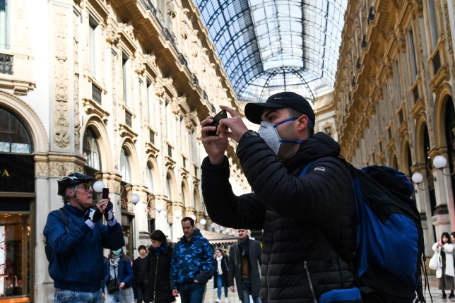A man wearing a protective facemask takes pictures with his mobile phone at the Gallery Vittorio Emanuele II, in central Milan, on February 24, 2020 following security measures taken in northern Italty against the COVID-19 the novel coronavirus. - Italy reported on February 24, 2020 its fourth death from the new coronavirus, an 84-year old man in the northern Lombardy region, as the number of people contracting the virus continued to mount. (Photo by ANDREAS SOLARO / AFP) (Photo by ANDREAS SOLARO/AFP via Getty Images)