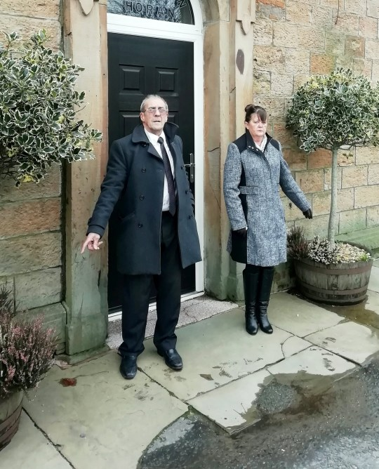Ann Bentley & John Harpur outside the funeral home. A council has apologised after two enforcement officers 'lay in wait' before pouncing on two mourners outside a funeral home and fined them for throwing away fag ends. See SWNS story SWLElittering. Ann Bentley was chased inside the home and fined ??80 along with friend John Harpur after being accused of throwing away cigarette butts by the two officers. The pair say they had placed their butts in two flower pots and had been left 'disgusted' by their treatment outside the home in Burnley, Lancs. CCTV footage shows the two officers pull up in a car opposite the Alderson and Horan funeral home after spotting the pair smoking outside. They then run towards the couple when they have finished their cigarettes to accuse them of littering. Today Burnley Council confirmed it had apologised and waive the fixed penalty notices. The pair had been attending the funeral of their friend, Dougie Wise, 73, at the funeral home last Thursday (20/2), before following the funeral cortege to Burnley Cemetery.