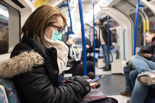 A woman wearing a facemark on the London Underground