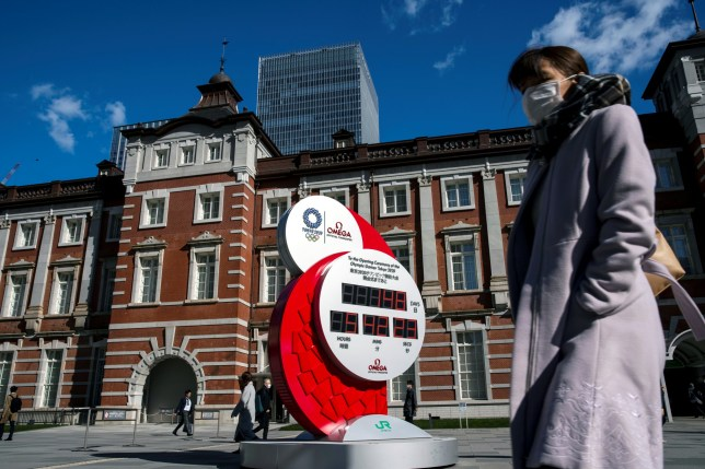 A woman wearing a protective face mask, following an outbreak of the coronavirus, stands in front of the big Omega One-Year Countdown clock for the opening ceremony of the Tokyo 2020 Olympic outside of Tokyo Station in Tokyo, Japan, February 27, 2020. REUTERS/Athit Perawongmetha