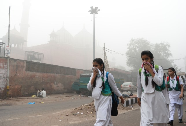 TOPSHOT - Indian schoolchildren cover their faces as they walk to school amid heavy smog in New Delhi on November 8, 2017. Delhi shut all primary schools on November 8 as pollution levels hit nearly 30 times the World Health Organization safe level, prompting doctors in the Indian capital to warn of a public health emergency. Dense grey smog shrouded the roads of the world's most polluted capital, where many pedestrians and bikers wore masks or covered their mouths with handkerchiefs and scarves. / AFP PHOTO / SAJJAD HUSSAIN (Photo credit should read SAJJAD HUSSAIN/AFP via Getty Images)