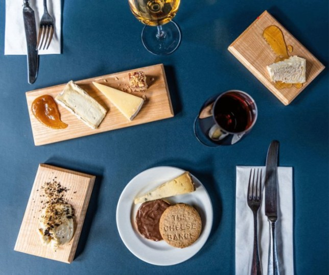 A birds-eye shot of a blue table with wooden platters of cheese on it, as well as two wine glasses