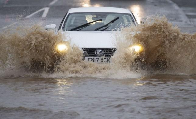 a car driving through a flood during storm jorge