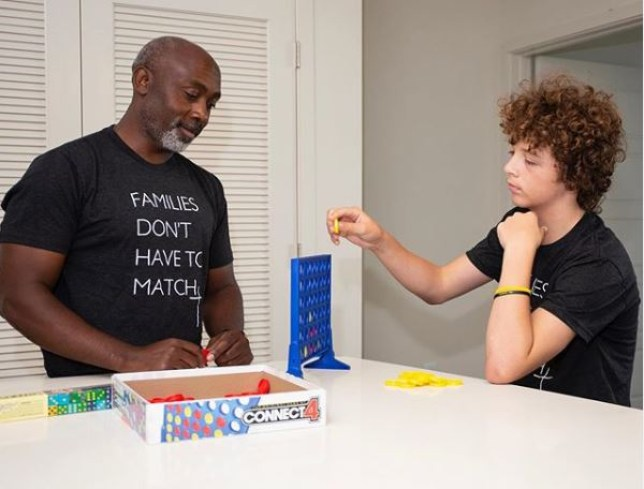 Peter Mutabazi and his adopted son Anthony playing Connect Four