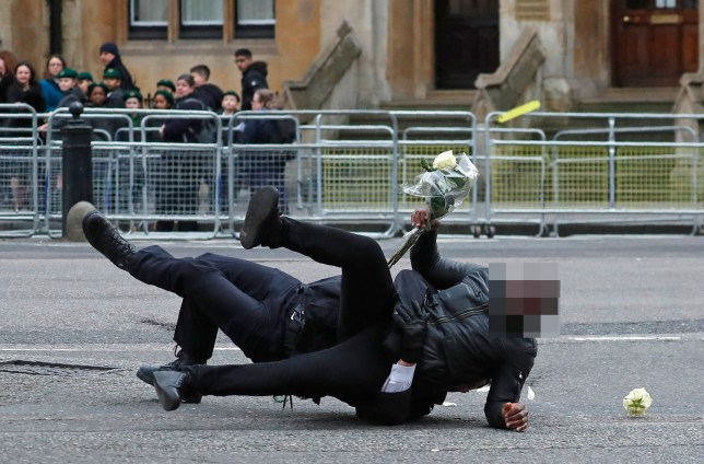 Police officers apprehend a protestor demonstrating against the government of Cameroon outside of the annual Commonwealth Day service at Westminster Abbey in London, Monday, March 9, 2020. The annual service organised by the Royal Commonwealth Society, is the largest annual inter-faith gathering in the United Kingdom. (AP Photo/Frank Augstein)