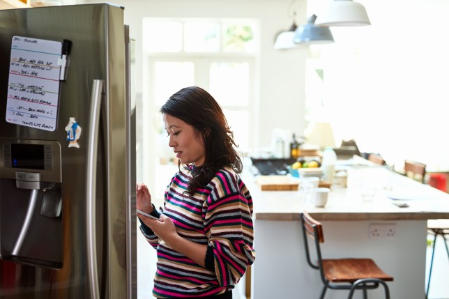 Woman at home in kitchen, using device to order groceries online.