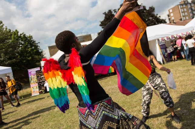 Person enjoys Black Pride with rainbow flag