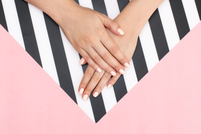 Woman's hands on pink and white background.