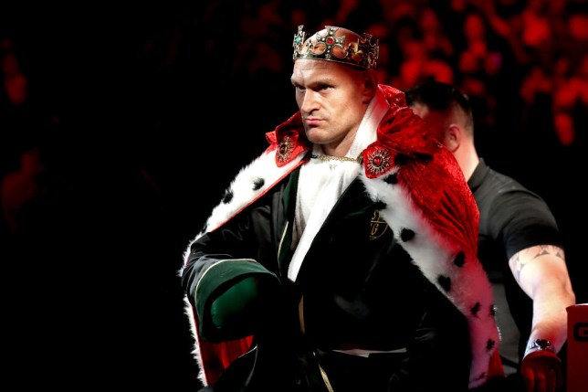 Heavyweight boxer Tyson Fury enters the ring dressed as a king