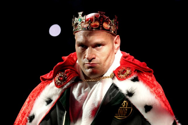 Tyson Fury is pictured in a crown and rob as he enters the ring before a fight