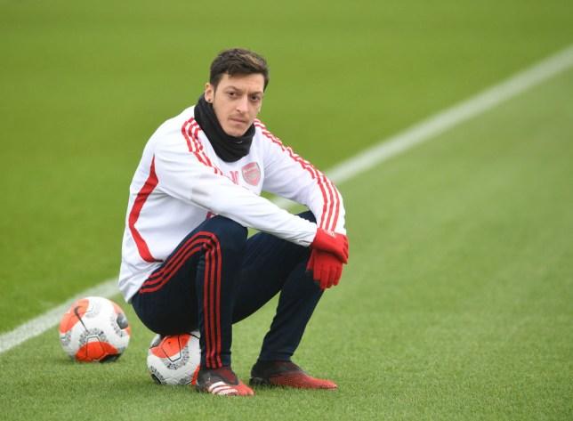 Mesut Ozil takes a break during Arsenal training