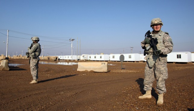 (FILES) In this file photo taken on December 29, 2014 US soldiers walk around at the Taji base complex which hosts Iraqi and US troops and is located thirty kilometres north of the capital Baghdad. - Katyusha rockets targeted an Iraqi airbase north of Baghdad hosting US-led coalition forces, the Iraqi military said on January 14, 2020 in the latest attack on installations where American troops are deployed. The statement from Iraq's military did not say how many rockets had hit Camp Taji but reported that there were no casualties. (Photo by ALI AL-SAADI / AFP) (Photo by ALI AL-SAADI/AFP via Getty Images)