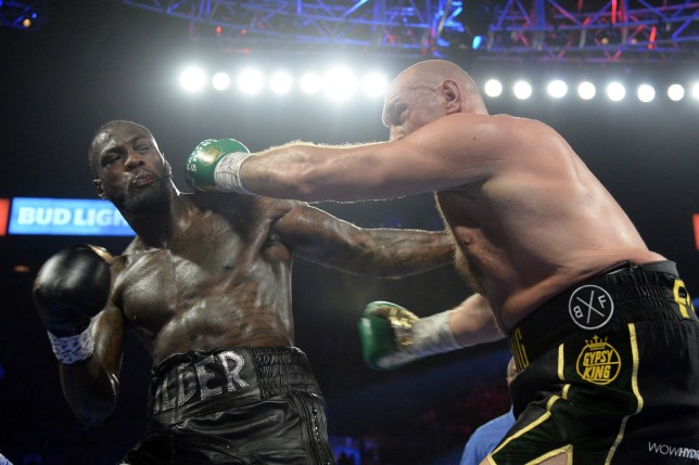 Tyson Fury aims a punch at Deontay Wilder during their boxing match