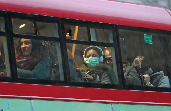 A woman wearing a face mask on a bus in London, as the first case of coronavirus has been confirmed in Wales and two more were identified in England - bringing the total number in the UK to 19. PA Photo. Picture date: Friday February 28, 2020. See PA story HEALTH Coronavirus. Photo credit should read: Yui Mok/PA Wire