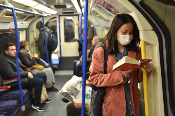 LONDON, ENGLAND - MARCH 02: A woman reads a book while wearing a face mask on the Picadilly Line tube train on March 02, 2020 in London, England. There has been thirteen more reported cases of the coronavirus - COVID-19 tested positive in the UK, bringing the total to thirty six. (Photo by John Keeble/Getty Images)