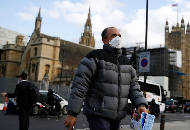 A man wearing a protective face mask is seen outside of the Houses of Parliament, in London, Britain March 12, 2020. REUTERS/Henry Nicholls