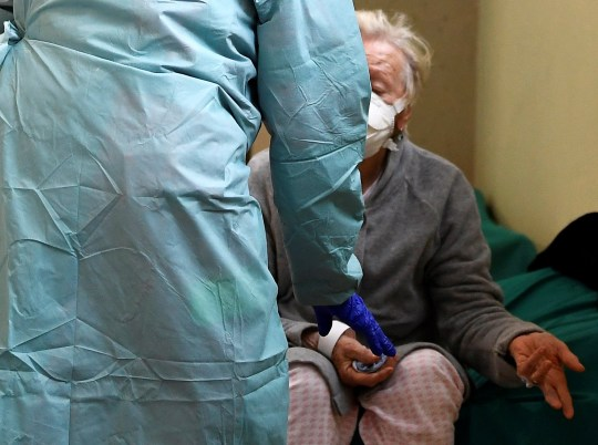 A patient wearing a protective face mask is helped by medical personnel inside the Spedali Civili hospital in Brescia, Italy March 13, 2020. REUTERS/Flavio Lo Scalzo