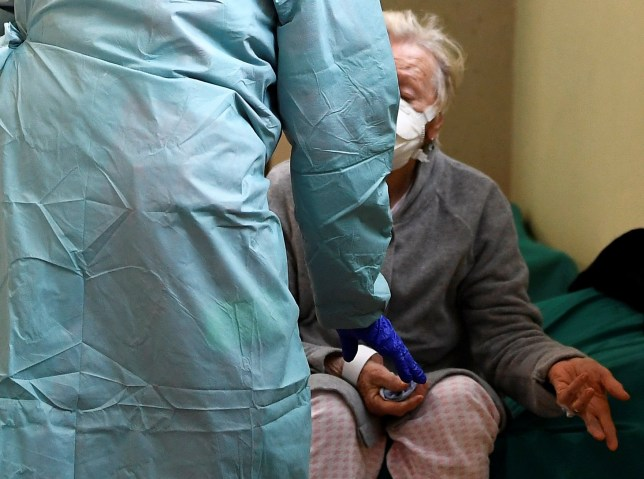 A patient wearing a protective face mask is helped by medical personnel inside the Spedali Civili hospital in Brescia, Italy March 13, 2020.