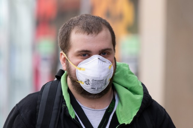 CARDIFF, UNITED KINGDOM - MARCH 14: A man wears a surgical face mask in Cardiff city centre on March 14, 2020 in Cardiff, United Kingdom. Coronavirus (Covid-19) has spread to over 149 countries in a matter of weeks, claiming over 5,600 lives and infecting nearly 150,000. There are currently 798 diagnosed cases in the UK and 11 deaths. (Photo by Matthew Horwood/Getty Images)