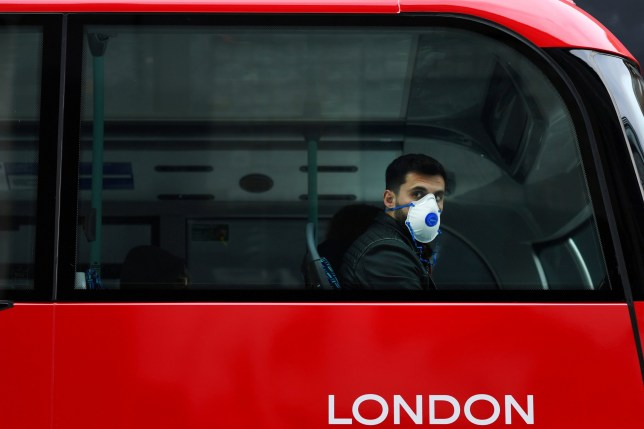 A man wears a mask while sitting on a bus, as the number of coronavirus cases grow around the world, in central London, Britain March 14, 2020. REUTERS/Dylan Martinez TPX IMAGES OF THE DAY